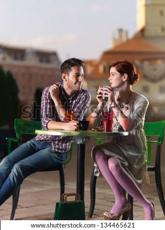 beautiful couple taking coffee in the city center on the terrace - stock photo