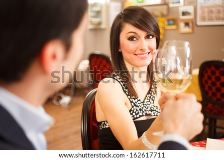 Beautiful couple toasting wineglasses in a restaurant - stock photo