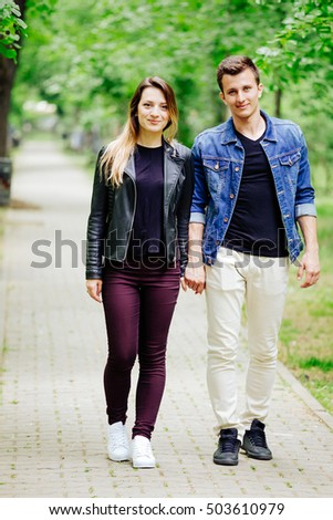 Beautiful couple walking in park while holding hands and smiling to camera