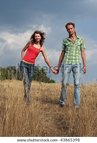 Beautiful couple walking in the field. They hold on to hands - stock photo