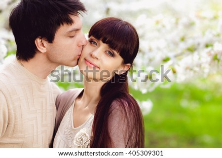 Beautiful couple walking near blossomed tree in the park. - stock photo