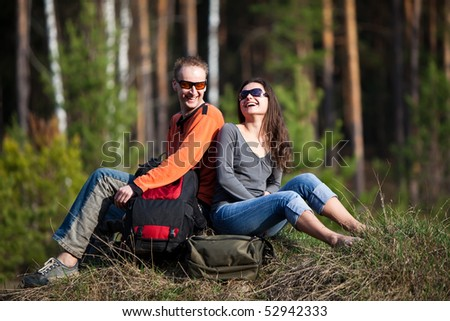 Beautiful couple with backpacks is having fun on the summer forest background.