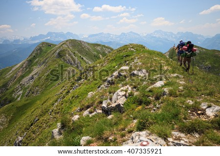 Beautiful couple with backpacks traveling in Visitor Mountains, Montenegro  - stock photo