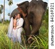 beautiful couple with elephant in wedding dress - stock photo