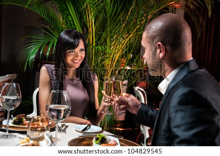 Beautiful couple with glasses of champagne at restaurant on romantic date