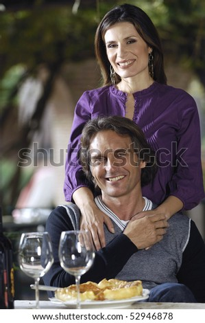 Beautiful couple with pies and wine - stock photo