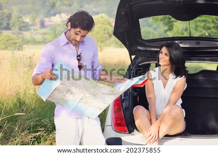 Beautiful couple with road map lost in the countryside . Tourism and journey