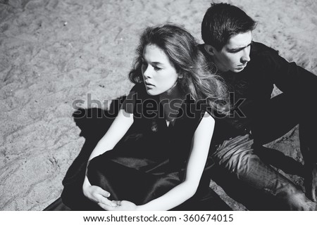 Beautiful couple. young girl and a man sitting facing away from each other - stock photo