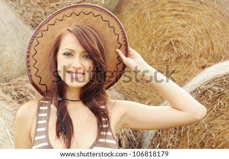 Beautiful cowboy girl on haystack background - stock photo