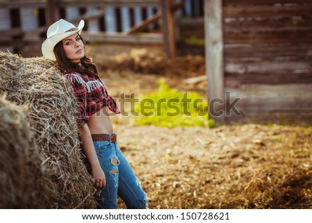 beautiful cowgirl style model posing on farmland, copy space - stock photo