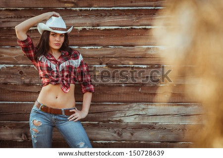 beautiful cowgirl style model posing on farmland near wood wall