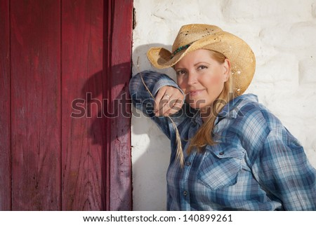Beautiful Cowgirl Wearing Cowboy Hat Leaning Against Old Adobe Wall and Red Door. - stock photo