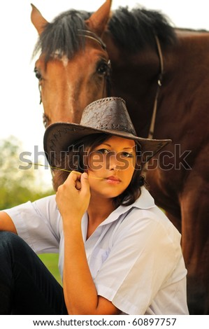 Beautiful cowgirl with her horse - stock photo