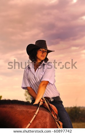 Beautiful cowgirl with her horse on sunset