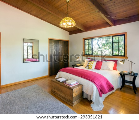 Beautiful Craftsman Bedroom with red cover, mirror and wooden floor. - stock photo