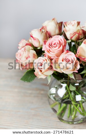 Beautiful cream and pink roses in vase - stock photo