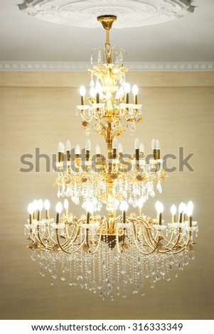 Beautiful crystal ancient chandelier in a hall. Lamp with soft yellow light - stock photo