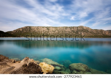 Beautiful crystal clear waters of Vouliagmeni Lake near Loutraki against a cloudy sky, Long exposure photography - stock photo