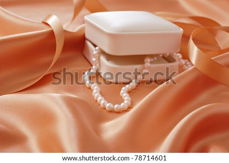 Beautiful cultured pearls cascading from jewelry gift box onto peach colored satin.  Macro with extremely shallow dof.  Selective focus limited to closest pearls. - stock photo