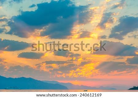 beautiful cumulus clouds over the sea at sunrise - stock photo