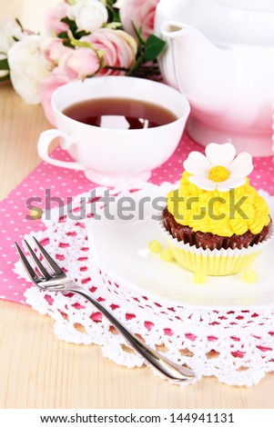 Beautiful cupcake and flavored tea on dining table close-up