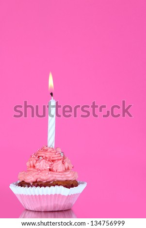 Beautiful cupcake with candle on pink background