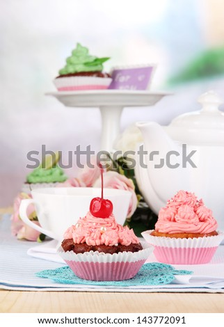 Beautiful cupcakes on dining table on room background