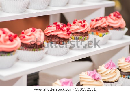 beautiful cupcakes with berries on display shelves - stock photo