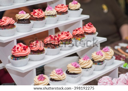 beautiful cupcakes with berries on display shelves
