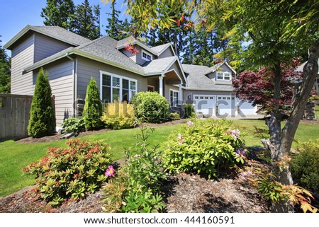 Beautiful curb appeal of classic American home with nice landscape design of the front yard. - stock photo