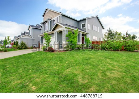 Beautiful curb appeal of large blue house and green front yard with well kept lawn. - stock photo
