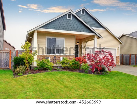 Beautiful curb appeal of sweet beige house with green front garden. View of porch with chairs. - stock photo