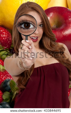 Beautiful curious woman looking through a magnifying glass