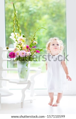 Beautiful curly baby girl in a white dress playing with a fresh flower bouquet next to a big window and door to the garden - stock photo