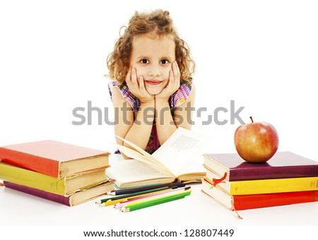 Beautiful curly girl with school books on the table. Isolated on a white background