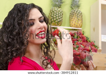 Beautiful curly hair girl tasting strawberries in fruit market - stock photo