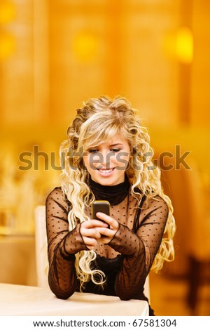 Beautiful curly-haired smiling girl sits at table and types text on mobile phone, against magnificent interior. - stock photo