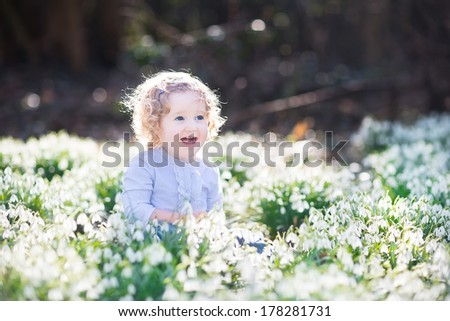 Beautiful curly laughing toddler girl playing with first spring flowers in a beautiful spring sunny park - stock photo