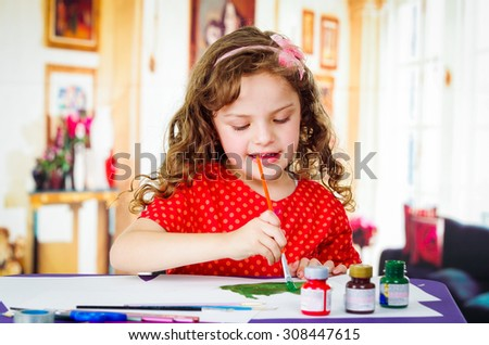 Beautiful curly little girl holding brush painting  - stock photo