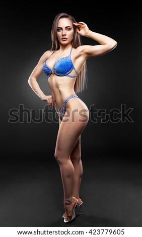 Beautiful curvaceous brunette woman posing in a blue bikini  - stock photo
