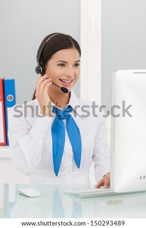 Beautiful customer service representative. Cheerful young female customer service representatives in headset working at the computer and smiling - stock photo