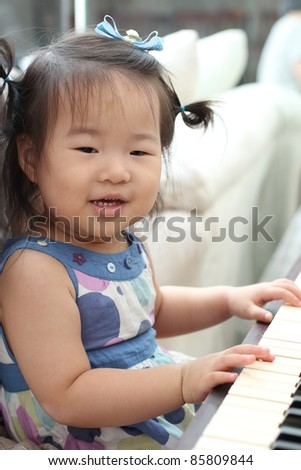 Beautiful Cute Asian Baby Toddler Girl with bows in hair playing piano
