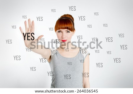 Beautiful cute attractive optimistic cheerful young woman with red lips feels happy and shows Yes sign on a white background - stock photo