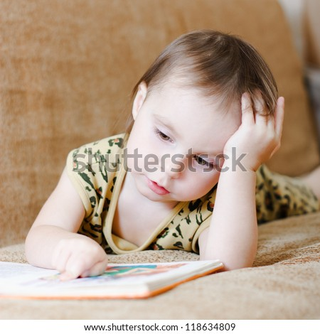 Beautiful cute baby reading a book while lying on the couch. - stock photo