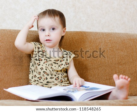 Beautiful cute baby reading a book while sitting on the couch. - stock photo