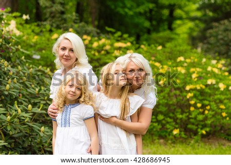 Beautiful cute blonde girl standing near flowers. Happy family outdoors in summer