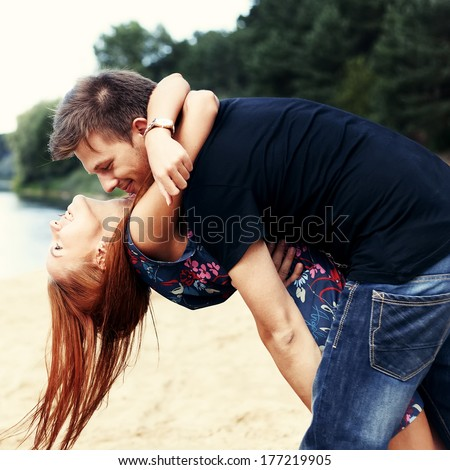 Beautiful cute couple on the beach near the water hugging - stock photo