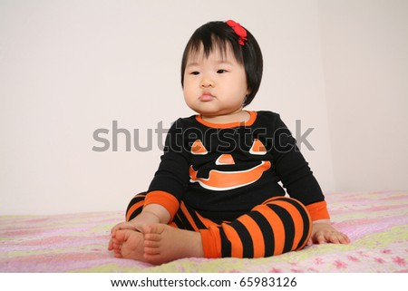 Beautiful Cute eleven month old baby asian infant girl in jack o lantern pajamas for halloween - stock photo