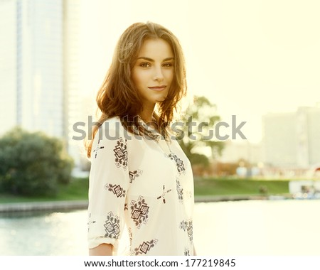 Beautiful cute girl on a sunny day walking in the park - stock photo