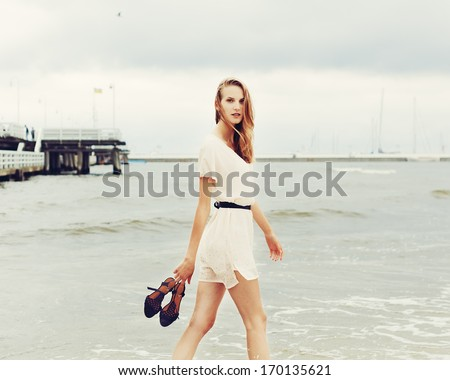 Beautiful cute girl summer walks along the beach barefoot with shoes in hands - stock photo